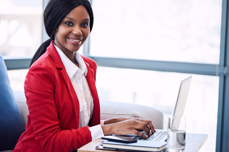 Black business woman looking at camera while smiling, with her hands still on the keyboard of her laptop computer where she was sitting working before looking up at camera. Reklamní fotografie