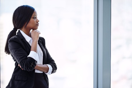 African busineswoman wearing black looking out windowwhile thinking about her future investments that need to be grown for her retirement to allow her financial security.