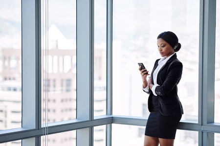 Professional adult female businesswoman busy texting on her cellphone while wearing a white shirt and formal black outfit while standing in front of large glass windows.