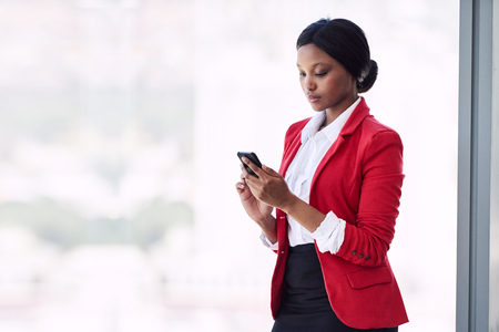 Young formally dressed adult woman busy using her mobile phone while standing in front of large glass windows while wearing a bright red blazer with copy space to her left.