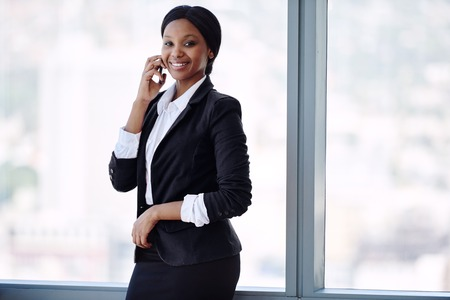 happy black businesswoman smiling while taling on her cellphone and smiling at the camera while dressed in a formal black outfit standing in front of large windows.