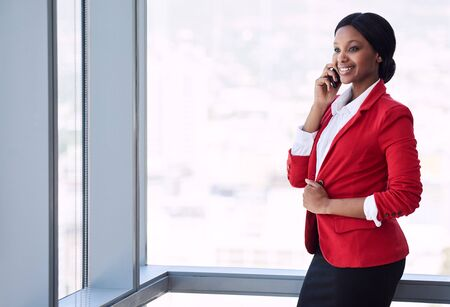 Happy black businesswoman looking off into the distance while smiling and talking on the phone, holding her blazer with one hand.