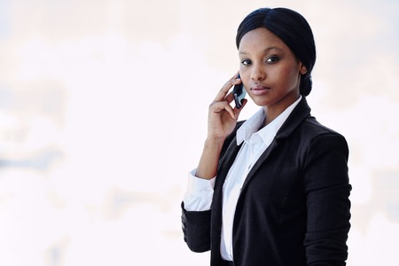 Young attractive, well dressed black businesswoman looking at camera with a serious facial expression while holding her phone against her ear in her right hand Reklamní fotografie