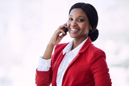 Attractive young black businesswoman smiling at the camera while talking on her mobile phone that she is holding in her right hand, all while looking good in her red and white outfit. Reklamní fotografie