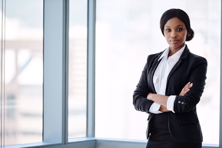 formally dressed african business woman looking into the camera with her arms crossed while standing in front of large glass windows with a cityscape behind her.