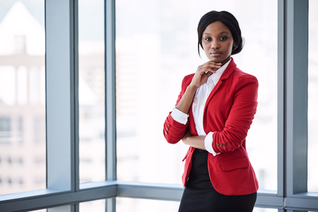 Confident businesswoman looking at the camera with bold body language while wearing a red blazer with large windows behind her in the background. Reklamní fotografie
