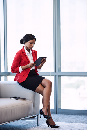 Young black businesswoman sitting on the edge of a sofa in a business lounge while looking at the screen of the digital tablet that she is holding in her hands. Reklamní fotografie