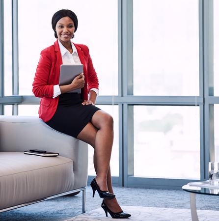 square image of well dressed young black corporate woman wearing a red jacket, holding a digital tablet while sitting on the edge of the couch in a modern business lounge.