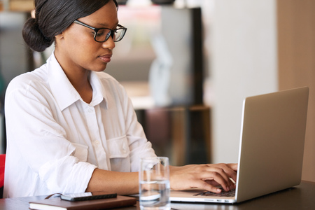 Young adult black female student busy typing out her assignment on her new modern laptop, wearing a crisp white shirt and a pair of black spectacles, while sitting at her desk at home.