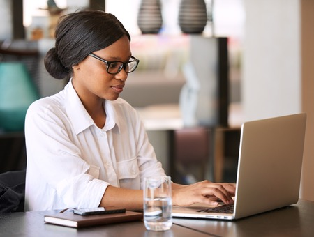 Accomplished young black businesswoman busy typing on her notebook computer while seated at her dining table at home, weating prescription glasses to see better.