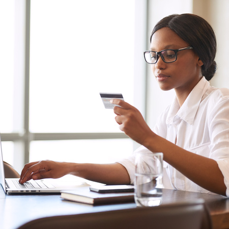Square image of beautiful young black female busy holding a credit card in one hand reading off the required information and typing in the relevant digits to make payments for her online shopping.