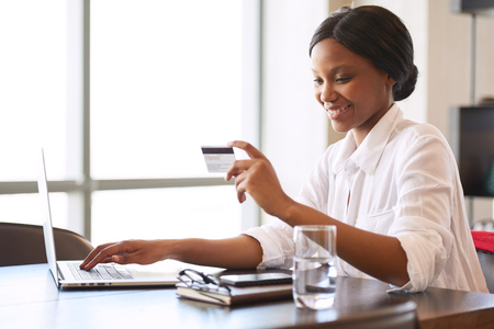 Young black woman smiling happily while making electronic payments with the use of her credit card that she is holding in one hand while typing with the other.