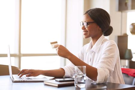 若い黒女子学生の自宅で彼女の机に座っている間彼女のノート パソコンを使用してオンライン彼女の授業料の支払を作る忙しい眼鏡のフレーム彼女 写真素材