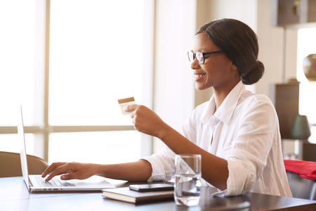 젊은 흑인 여성 학생 바쁜 집 지불 그녀의 책상에 앉아있는 동안 그녀의 랩톱 컴퓨터를 사용 하여 온라인 지불 그녀의 어두운 안경 액세사리와 함께 바