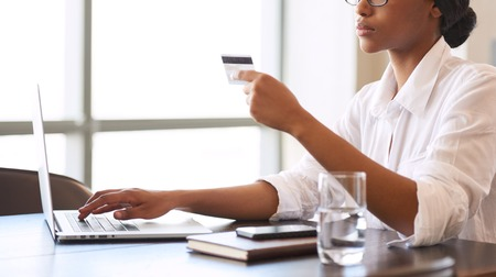 Faceless african american woman making wire transfers online using her credit card details to verify the transaction, to ensure her business relations remain stable.