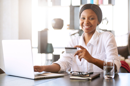 Good looking young black woman smiling at the camera while seated in front of her computer at her dining room table behind her notebook where she is making online payments with her credit card. Reklamní fotografie
