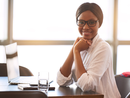 Young black woman wearing glasses looking at camera with a big smile resting her head on her hands while leaning on the desk with her elbows and large windows behind her.