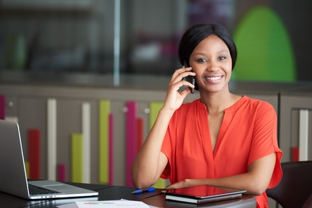 Young black female employee wearing a casual outfit while sitting at work in the office smiling at the camera while she is talking on her phone.