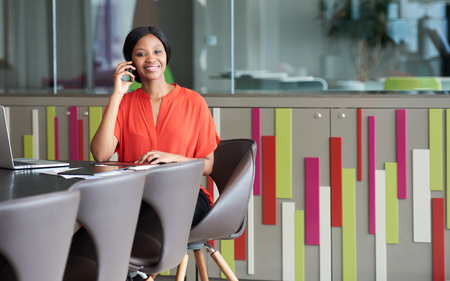 Colourful image of young black businesswoman sitting at a conference table in a modern office space while smiling at the camera and holding a phone against her ear.