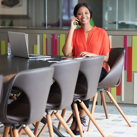 Square image of young african business woman sitting at the end of a conference table while talking on the phone and smiling at the camera. Stock Photo