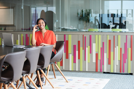 Full body image of an attractive young african american woman sitting on a beautiful brown chair at the end of a conference table in the business lounge of her office building.