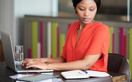 다채로운 사무실 공간에 앉아서 밝은 오렌지색 블라우스를 입은 동안 잘 읽는 동안 잘 읽는 성인 흑인 사업가 바쁜 입력