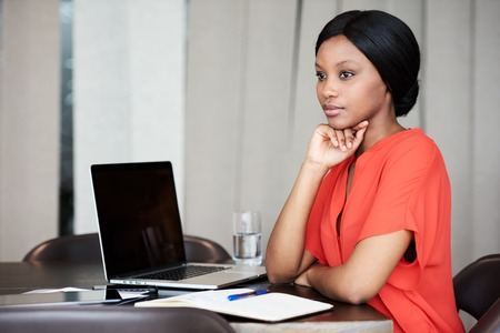 Composed young black businesswoman looking off into the distance while sitting at her office desk at work, wearing a bright orange blouse in her workspace.