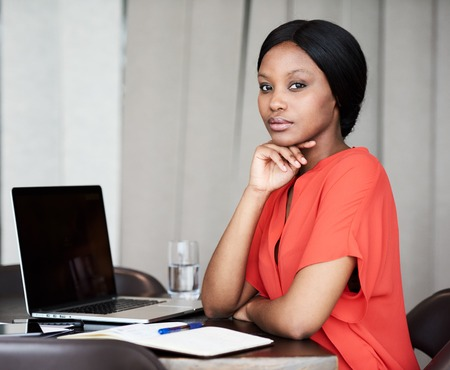 Attractive young adult businesswoman looking into the camera confidently while sitting at her desk in her work space while resting her head on her hand.