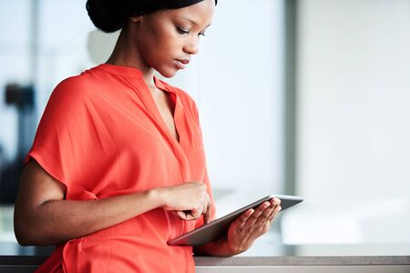 Attractive businesswoman wearing a bright orange blouse while looking at the screen of the digital electronic tablet that she is busy using with large bright windows in the background. Reklamní fotografie