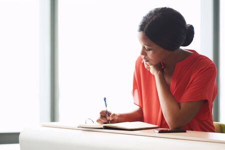 Self employed black female entrepreneur busy writing in her notebook while seated at a desk with a large bright window behind her in the background.
