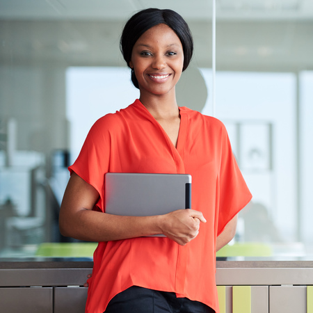 Square portrait of black entrepreneur holding a digital tablet while smiling happily at the camera wearing a bright orange shirt while standing in her usual business environment. Stock Photo