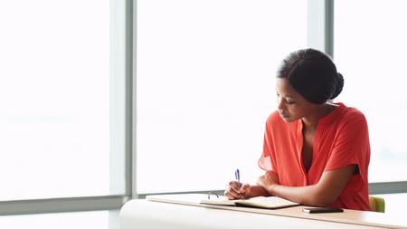 성인 여성 아프리카 작가 그녀가 장착되어 비즈니스 라운지에서 유리의 큰 창 옆에 앉아있는 동안 밝은 오렌지 블라우스를 입고있는 동안 그녀의 노트