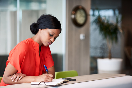 Authentic image of African American woman busy using a pen to write down her shedule that she has planned out in her notebook while sitting in the colourful business lounge.