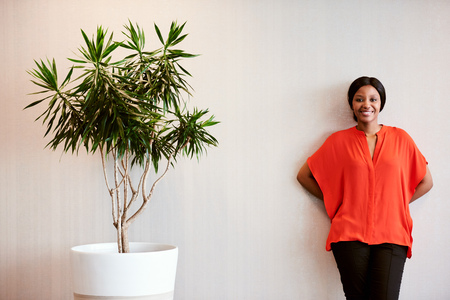 Black female wearing a bright orange blouse while smiling at camera and standing next to a tree planted in a pot as a sign of support for the environment. Reklamní fotografie