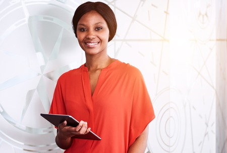 black businesswoman smiling at camera while holding an electronic tablet in one hand and standing in front of a textured glass wall with some flare leaking in from behind. Reklamní fotografie