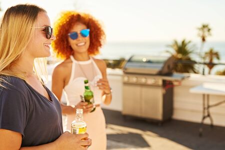 Two beautiful woman holding alcoholic ciders with smiles on their faces while standing on a rooftop at a barbecue with a stunning ocean view on a warm summers day. Reklamní fotografie