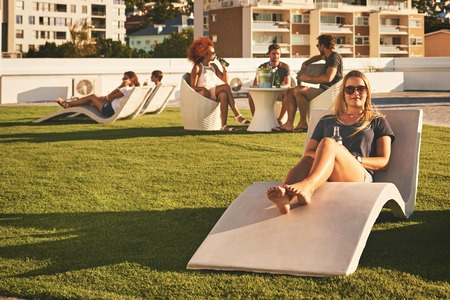 Beautiful young girl looking at the camera while lying down on a sun bed, holding an alcoholic beverage in her hand with a group of people socialising behind her in the background. Reklamní fotografie