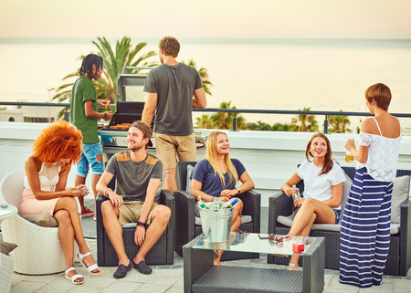 Groupe d'amis attrayant socialisng sur un toit avec une vue stupéfiante sur l'océan sur une soirée d'été parfaite avec un délicieux barbecue et des boissons alcoolisées. Banque d'images