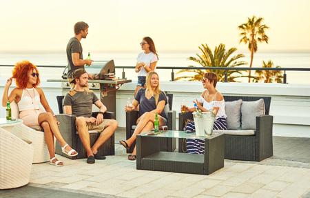 Hermoso grupo de personas que se socializan en un tejado con algunas bebidas alcohólicas y parrilla de barbacoa va, mientras que el remojo es un poco de sol de verano al aire libre. Foto de archivo