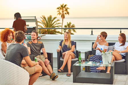 Attractive group of young people socialising on a rooftop with a view of the ocean while enjoying some alcoholic beverages and a gas barbecue on a warm summer sunset. Reklamní fotografie