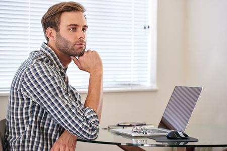 若い男は、彼の仕事を先延ばし、距離に思慮深く見て
