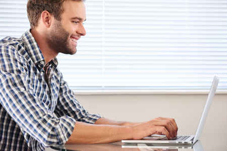 profile image of handsome groomed man typing on laptop computer