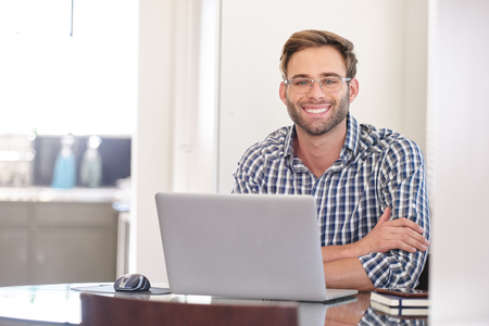 Handsome groomed caucasian accountant smiling while looking at camera Reklamní fotografie