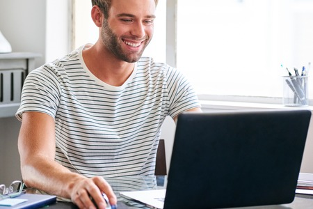 Happy young male student smiling while seated behind his laptop