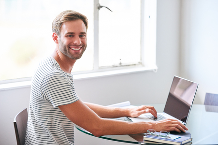 handsome young male student smiling at camera seated behind laptop Reklamní fotografie