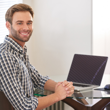 Handsome young man sitting behind his laptop in his living room at a glass table, smiling at the camera over his shoulder with a positive and productive energy.