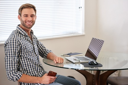 Handsome young white man sitting indoors in his house at his glass desk behind his modern notebook and technology, with his body turned sideways towards the camera with a big smile. Reklamní fotografie - 79936698