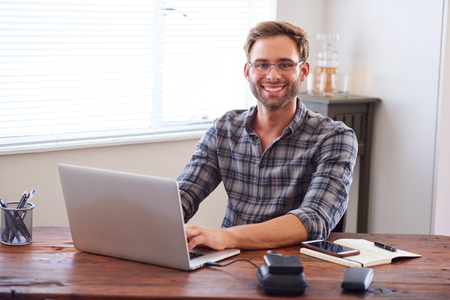 Attractive young, well groomed caucasian male entrepreneur and businessman smiling at the camera with his hands on the keyboard of his laptop computer. Reklamní fotografie - 79937547
