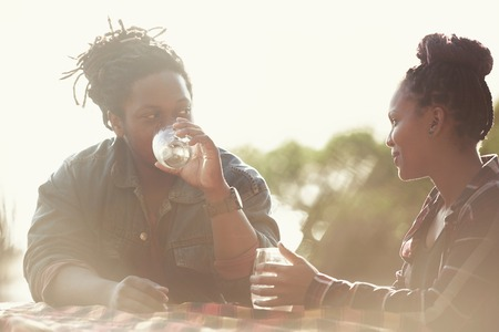 black guy with dreads taking a sip of his alcoholic beverage while on a date with an attractive multi ethnic woman whom looks like she is enjoying his conversation. Reklamní fotografie