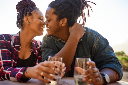 Interracial couple on a date outdoors with drinks sitting at a table during golden hour before sunset about to kiss for the first time by her new life partner and lover. Reklamní fotografie